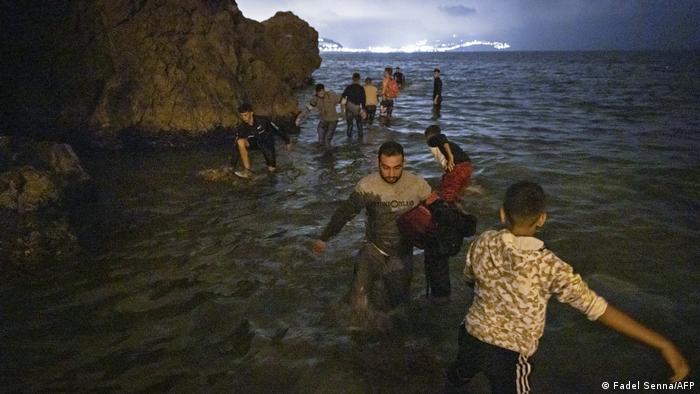 Los migrantes caminan en aguas poco profundas en Fnideq, Marruecos.