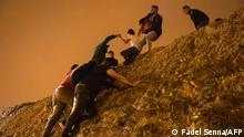 Moroccan migrants climb a rocky cliffside as a policeman watches in the northern town of Fnideq as they attempt to cross the border from Morocco to Spain's North African enclave of Ceuta on May 18, 2021. - At least 5,000 migrants, an unprecedented influx at a time of high tension between Madrid and Rabat, slipped into Ceuta on May 17, a record for a single day, Spanish authorities said. They reached the enclave by swimming or by walking at low tide from beaches a few kilometres to the south, some using inflatable swimming rings and rubber dinghies. (Photo by FADEL SENNA / AFP)