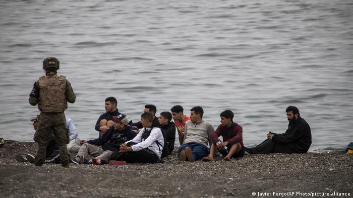 Hombres y niños marroquíes se sientan mientras el ejército español rodea un área en la frontera marroquí-española.