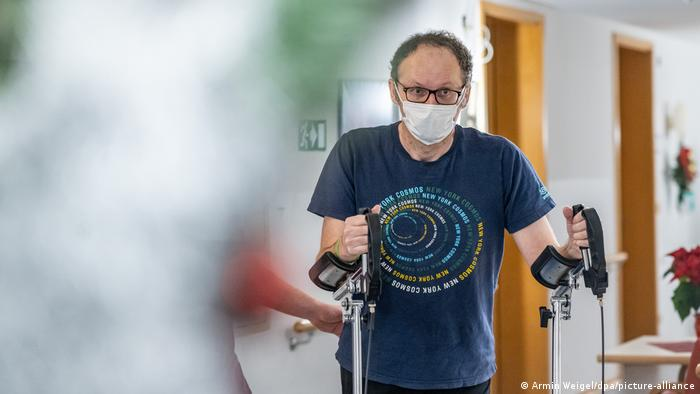 A man wearing a face mask uses crutches at a rehabilitation clinic