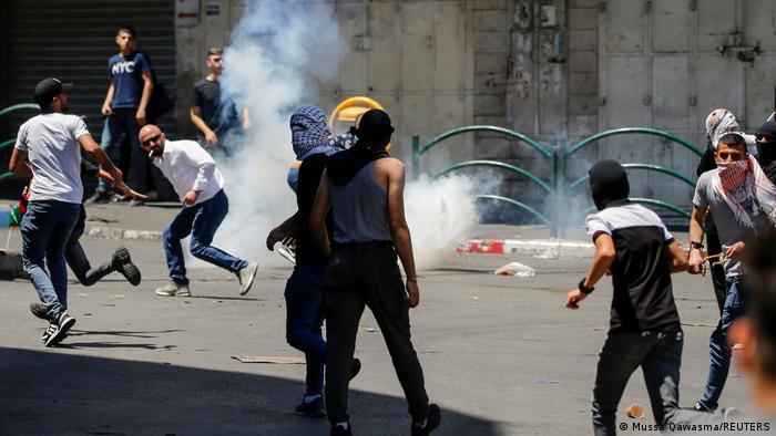 Palästinensische Demonstranten suchen Schutz vor von israelischen Sicherheitskräften eingesetztem Tränengas