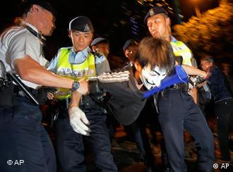 Pro-democracy protester is taken by the police officers at the government headquarter during the demonstration in Hong Kong Thursday July 1, 2010. Hecklers besieged Hong Kong's Democrats at the opposition camp's flagship protest march Thursday, accusing them of selling out their cause by striking a deal with Beijing on conservative electoral changes in the semiautonomous Chinese territory. Several protesters approached the several hundred Democratic Party members who took part in the demonstration, chanted