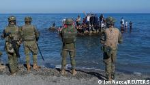 Moroccan citizens stand on the rocks in front of Spanish legionnaires at El Tarajal beach, near the fence between the Spanish-Moroccan border, after thousands of migrants swam across this border during last days, in Ceuta, Spain, May 18, 2021. REUTERS/Jon Nazca
