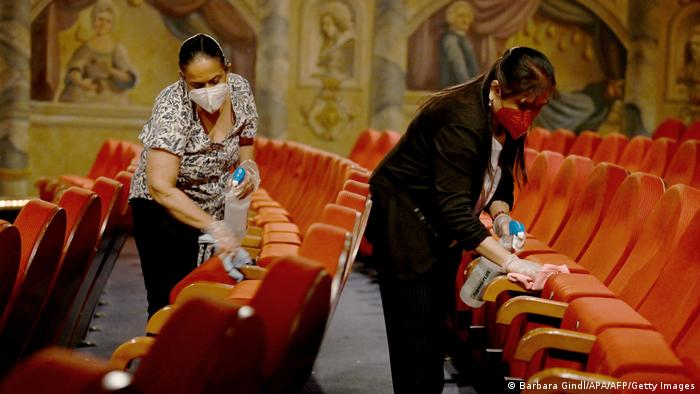 Two women wearing face masks cleaning orange theater chairs