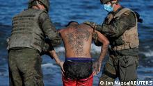 "*** Dieses Bild ist fertig zugeschnitten als Social Media Snack (für Facebook, Twitter, Instagram) im Tableau zu finden: Fach ""Images"" —> Weltspiegel/Bilder des Tages *** 18.05.21 *** Spanish legionnaires attend to a Moroccan citizen at El Tarajal beach, near the fence between the Spanish-Moroccan border, after thousands of migrants swam across this border during last days, in Ceuta, Spain, May 18, 2021. REUTERS/Jon Nazca"