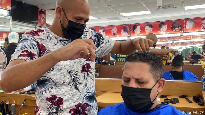 César Moncado cortando el pelo a un cliente