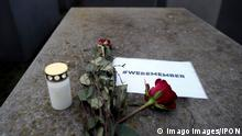 A candle, roses and a note reading #weremember - commemorating the liberation of Auschwitz