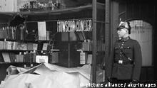 8-1938-11-9-A1-19 (1108415) Reichskristallnacht, Berlin, zerstörtes Geschäft/ Foto 1938 Deutschland, 'Reichskristallnacht', Nacht vom 9./10.Nov.1938 (Zerstörung jüd.Friedhöfe, Synagogen, Wohn- u.Ge- schäftshäuser durch NS-Trupps). - Berlin: Polizist vor dem Eingang einer Buchhandlung mit eingeschlagener Schaufensterscheibe. - Foto. |