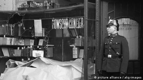 Historical photo of a German police officer in front of a bookstore that has been damaged.
