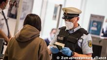 February 8, 2021, Freising Bei Muenchen, Bavaria, Germany: A federal police officer in the Munich International Airport checks the passport and documents of an arriving passenger. The Bavarian Interior Ministry in collaboration with the German Federal Police (Bundespolizei) and the Grenzpolizei (Border Police) held a presentation on their roles in fighting the Corona pandemic at airports. Part of the strategy to prevent the importation of the novel Coronavirus, particularly the mutant variants prevalent in South Africa, the United Kingdom, and Brazil involves the DEA Digital Entry Regulation, testing at the airports, quarantine, and an agreement from airlines to not transport passengers from risk areas. (Credit Image: © Sachelle Babbar/ZUMA Wire