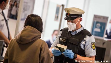 A border police officer checks documents at Munich International Airport