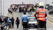 Police look on as people gather during demonstration to protest against the increase in the cost of living, corruption across the country, and to demand the holding of local elections, in Luanda on March 20, 2021. (Photo by Osvaldo Silva / AFP) (Photo by OSVALDO SILVA/AFP via Getty Images)