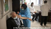 An Iranian elderly man wearing a protective face mask receives a dose of the China's Sinopharm new coronavirus disease (COVID-19) vaccine, at the west Tehran health center on May 11, 2021. (Photo by Morteza Nikoubazl/NurPhoto)
