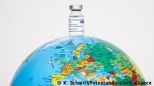 Bamberg, Deutschland 13. Mai 2021: Auf einer Weltkugel steht eine Ampulle mit dem COVID-19-Vektor-Impfstoff von AstraZeneca .