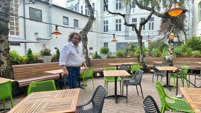 Vincenzo Berenyi walking past empty tables on his restaurant's terrace