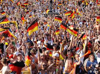 A crowd of German fans wave flags and celebrate