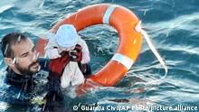 In this photo provided by the Spanish Civil Guard in Ceuta, Spain, on Tuesday May, 18, 2021, a member of the civil guard rescues a baby that was separated from its parents, who were migrants, in the sea off Ceuta, Spain. Spain's North African enclave of Ceuta is facing a humanitarian crisis after thousands of migrants swum around or jumped a border fence left unguarded by Morocco as part of a diplomatic row with its European neighbor. (Guardia Civil via AP)