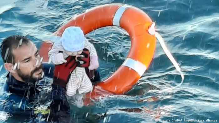 A member of the civil guard rescues a baby that was separated from its parents, who were migrants, in the sea off Ceuta, Spain