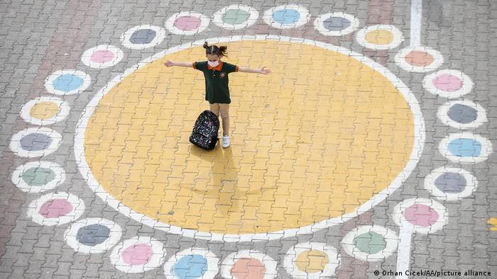 A pupil standing in the middle of a social distancing circle
