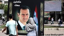 People walk past a banner set up by a private citizen showing Syria's President Bashar al-Assad with accompanying text in Arabic reading we will continue with you at Arnous Square in the capital Damascus on May 10, 2021 ahead of the country's presidential elections. - A Syrian former minister and a member of the Damascus-tolerated opposition will face Assad in the May 26 presidential election, according to the constitutional court in Syria. The election will be the second since the start of a decade-long conflict that has killed over 388,000 people and forced more than half of Syria's pre-war population from their homes. (Photo by LOUAI BESHARA / AFP)
