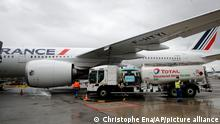 Workers refuel an Airbus A350 with sustainable aviation fuel at Roissy airport, north of Paris, Tuesday, May 18, 2021. Air France-KLM is sending into the air what it calls its first long-haul flight with sustainable aviation fuel Tuesday. The plane is said to be using petroleum mixed with a synthetic jet fuel derived from waste cooking oils. (AP Photo/Christophe Ena)