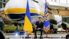 Ukrainian President Volodymyr Zelenskyy gestures while speaking to media during a news conference with the world's largest airplane, Ukrainian Antonov An-225 Mriya in the background at the Antonov aircraft factory in Kyiv, Ukraine, Thursday, May 20, 2021. (AP Photo/Efrem Lukatsky)