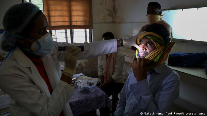 A doctor checks a patient who recovered from COVID-19 but is now infected with black fungus at the Mucormycosis ward of a government hospital in Hyderabad, India