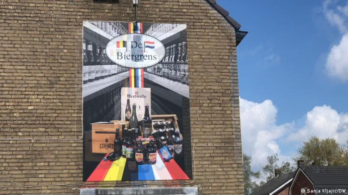 Advertisement for 'Biergrens' showing beer bottles on the colors of the Belgian and Dutch flags