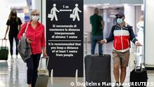 FILE PHOTO: Passengers wearing protective face masks walk at Fiumicino Airport on the day EU governments agreed a safe list of 14 countries for which they will allow non-essential travel starting from July, following the coronavirus disease (COVID-19) outbreak, in Rome, Italy, June 30, 2020. REUTERS/Guglielmo Mangiapane/File Photo