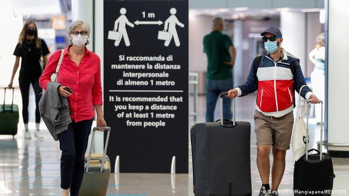 Passengers wearing protective face masks walk at Fiumicino Airport