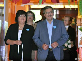 Parliament Speaker, acting president Bronislaw Komorowski with wife Anna enter a voting station in Mackowa Ruda, northeast Polan, Sunday, July 4, 2010. Poles are choosing their new president in the runoff presidential elections, between Komorowski and Jaroslaw Kaczynski, twin brother of the late President Lech Kaczynski who was killed in a plane crash.(AP Photo/Alik Keplicz)