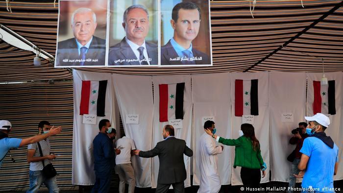 Wahllokal für syrischere Bürger im Libanon in einem Zelt. Die Wahlkabinen sind mit Tüchern abgeteilt, an denen syrische Flaggen befestigt sind. Von der Decke hängen Porträts der drei Kandidaten. Ordner weisen den Wählern freie Wahlkabinen zu.