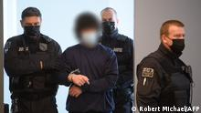Defendant Abdullah A. (C), accused of stabbing a German tourist to death in Dresden, is led by court officials into the hearing room on the last day of his trial at the Higher Regional Court in Dresden, eastern Germany, on May 21, 2021. - The trial of a Syrian jihadist who stabbed a German tourist to death in an apparently homophobic attack last year began in the eastern city of Dresden on April 12, 2021. The 21-year-old, named by German media as Abdullah A., is charged with murder, attempted murder and dangerous bodily harm for attacking two men who had travelled to Dresden from North Rhine-Westphalia with a knife on October 4, 2020. (Photo by Robert Michael / POOL / AFP) / German court requests that the face of the defendant must be made unrecognizable