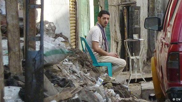 Man sitting in a chair in a heap of rubble