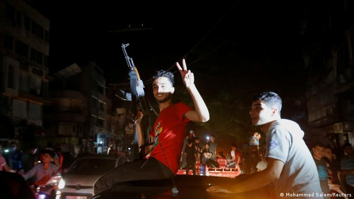 Palestinians celebrating in streets of Gaza City, one holding a gun pointed upward