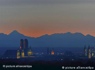 Panoramic view of Munich skyline with the sun setting behind the Alps