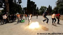 Palestinians react as Israeli security forces throw stun grenade during clashes at the compound that houses Al-Aqsa Mosque, known to Muslims as Noble Sanctuary and to Jews as Temple Mount, in Jerusalem's Old City May 21, 2021. REUTERS/Ammar Awad