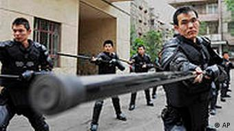 In this Saturday, July 3, 2010 photo, policemen take part in a daily training at a police station in Urumqi, in northwest China's Xinjiang region. Teams of police patrolled streets in the western region of Xinjiang on Monday as stringent security was imposed for the one-year anniversary of China's worst ethnic violence in decades. (AP Photo) ** CHINA OUT **