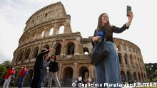 People take selfies outside the Colosseum on the day of its reopening, as much of the country becomes a 'yellow zone', easing coronavirus disease (COVID-19) restrictions, in Rome, Italy, April 26, 2021. REUTERS/Guglielmo Mangiapane