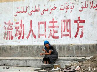 A Uighur woman sits under an official slogan says in Chinese Population flow spread in all directions at Uighur sector in Urumqi, western China's Xinjiang province, Tuesday, July 14, 2009. The capital of China's western Xinjiang region was tense amid tight security Tuesday, a day after police fatally shot two Uighur men and wounded a third, more than a week after deadly ethnic rioting. (AP Photo/Eugene Hoshiko)