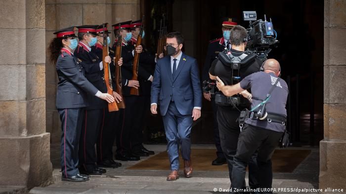 Masked Pere Aragones walks out of the Catalan parliament, surrounded by guards and reporters