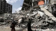 Israel and Hamas cease fire across the Gaza Strip - Palestinians walk past the ruins of a building destroyed in an Israeli air strike in the recent cross-border violence between Palestinian militants and Israel, in Gaza May 21, 2021. REUTERS/Suhaib Salem