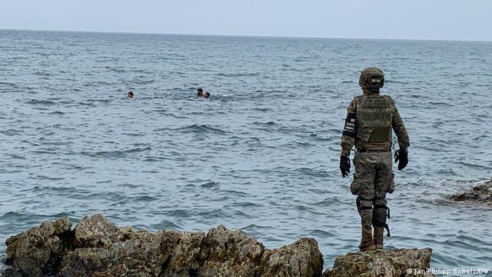 Un soldado español observa a la gente nadando hacia la playa de Ceuta