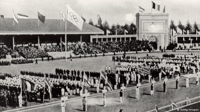 Imagem em preto e branco mostra cerimônia de abertura dos Jogos da Antuérpia. É possível ver no estádio a bandeira olímpica.
