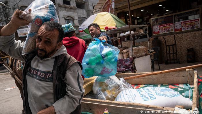 فلسطينيون يتلقون مساعدات الأونروا في غزة