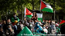 Protesters hold Palestinian flags in Paris, Saturday, May 22, 2021, as they take part in a rally supporting Palestinians. Egyptian mediators held talks Saturday to firm up an Israel-Hamas cease-fire as Palestinians in the Hamas-ruled Gaza Strip began to assess the damage from 11 days of intense Israeli bombardment.Supporters of the Palestinians. (AP Photo/Thibault Camus)