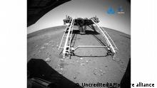 In this image released by the China National Space Administration (CNSA) on Saturday, May 22, 2021, a landing platform and the surface of Mars are seen from a camera on the Chinese Mars rover Zhurong. China's first Mars rover has driven down from its landing platform and is now roaming the surface of the red planet, China's space administration said Saturday. (CNSA via AP)