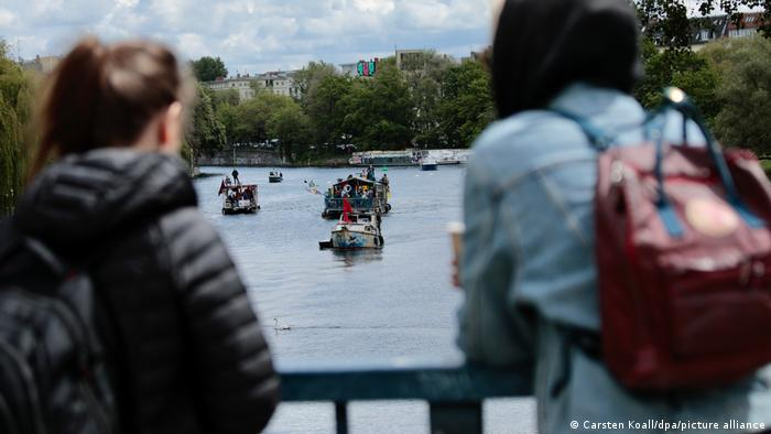 Two girls watch the protesters' boats on the river Spree