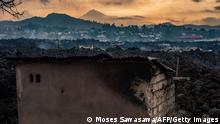 TOPSHOT - This general view shows a structure still standing, surrounded by the lava who flew during yesterday's eruption on May 23, 2021. - A river of boiling lava came to a halt on the outskirts of Goma Sunday, sparing the city in eastern DR Congo from disaster after the nighttime eruption of Mount Nyiragongo sent thousands of terrified residents fleeing in panic. Fire and strong fumes emanated from the blackish molten rock as it swallowed up houses, heading towards Goma airport on the shores of Lake Kivu. (Photo by Moses Sawasawa / AFP) (Photo by MOSES SAWASAWA/AFP via Getty Images)