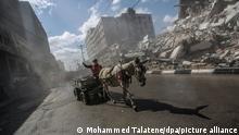 Ein Mann fährt mit einen Wagen voller Schutt eine Straße entlang. Nach der Waffenruhe zwischen Israel und der Hamas werden die verheerenden Zerstörungen im Gazastreifen deutlich. +++ dpa-Bildfunk +++